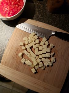 raw paneer cut into cubes on cutting board